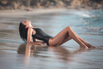 beautiful girl with a perfect body lying on the beach, by the se