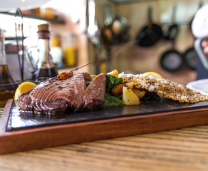 Grilled tuna stake with potato and lemon served on stone plate