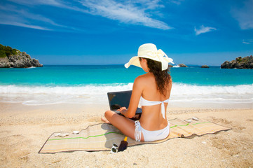 Beautiful woman with laptop computer on beach.