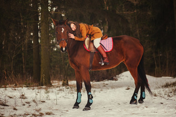 brunette walking outdoors on the horse. Winter park.