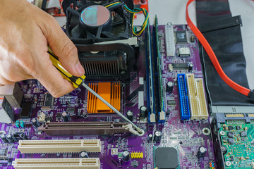 Technician's hands fixing mainboard with screwdriver