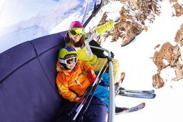 Little boy with mother on ski chair lift