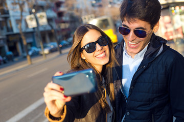Happy young couple taking selfies with smartphone.