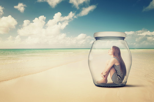 woman sitting in jar on beach looking at the ocean view