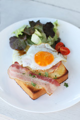 Plate of breakfast with fried egg, bacon and toast
