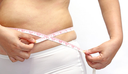 woman with little fat  measuring her stomach