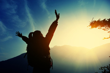 cheering woman open arms at sunrise mountain peak