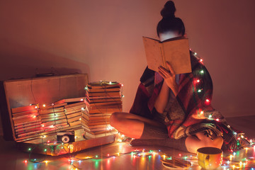 girl reading a book under blanket at home in cold weather
