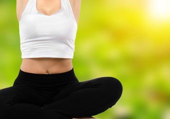 Portrait of pretty young woman doing yoga exercise with blurred