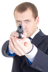 serious man in business suit aiming gun at camera isolated on wh