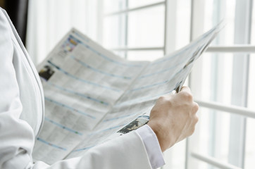 Woman reading business news in front of window