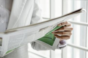 Closeup of businesswoman hand holding newspaper