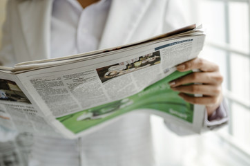 Business person reading newspaper in office