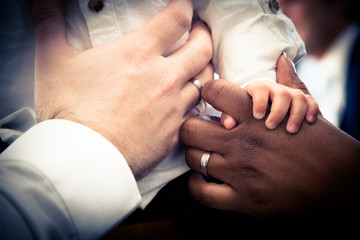 Hands of Interracial couple with child