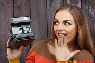 beautiful girl with old retro camera  on the wooden background