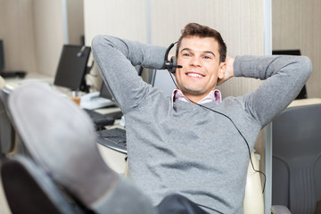 Relaxed Smiling Customer Service Representative With Legs On Des