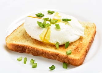 Poached egg on bread over white plat