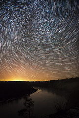 beautiful night sky, spiral star trails and the forest