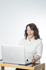Young woman with surprise expression in front of laptop