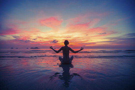 Woman doing meditation near the ocean beach.