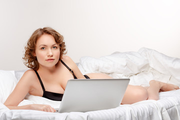 Portrait of woman lying on bed with a laptop