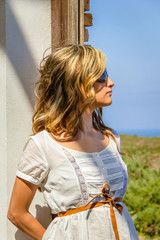 Curly blonde girl with white dress and sunglasses