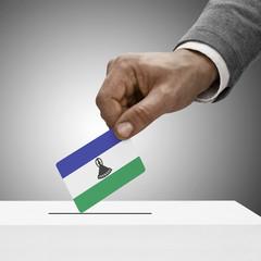 Black male holding flag. Voting concept - Lesotho