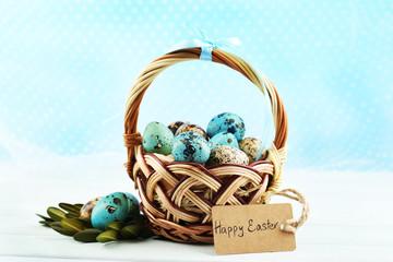 Bird eggs in wicker basket on bright background