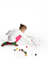 Little girl is drawing on white floor.