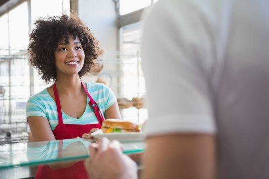 Pretty waitress giving sandwich to customer