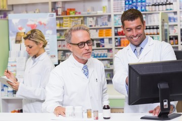 Team of pharmacists looking at computer