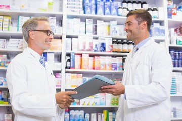 Smiling team of pharmacists holding clipboard