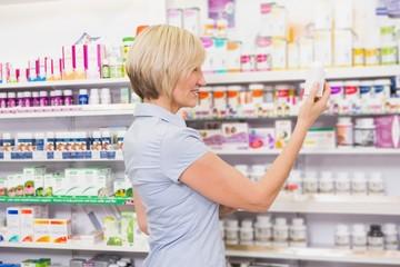 Pretty blonde customer looking at medicine