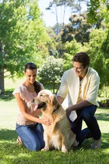 Happy couple with their pet dog in the park