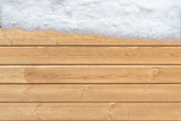 Wooden surface with snow on one side