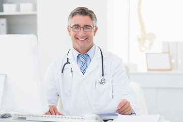 Happy male doctor reviewing documents at table