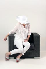 Frau mit Hut im Gartensessel