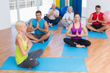 Female instructor with class meditating at gym