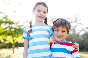 Happy siblings smiling at camera