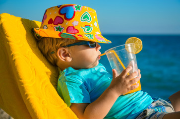 Foto op Canvas Sap Boy kid in armchair with juice glass on beach