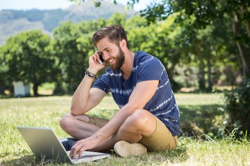 Handsome hipster using laptop in park