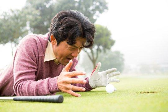 Golfer lying near golf ball