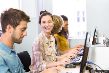 Student smiling at camera in computer class