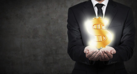 businessman holding gold dollar