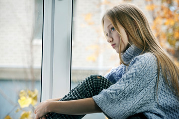 Rainy Day: Girl Sitting on the Window