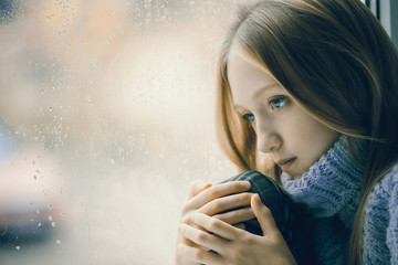 Rainy Day: sad Girl on the Window