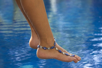 Female feet with ankle bracelet above the pool