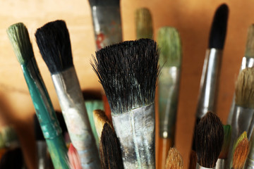 Different paintbrushes on wooden background