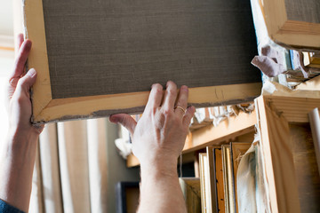 An artist taking canvas from shelving