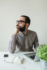 Busy man with beard in glasses thinking over laptop and smartpho